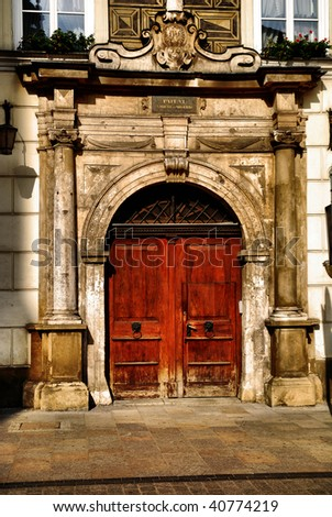 Old wooden door with ornament in stone wall. Krakow, Poland - stock photo