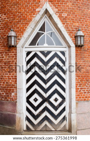 Old wooden door with rhombus black and white pattern and old brick wall. Vintage exterior details - stock photo