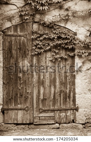 Old wooden door with rusty hinges of the antique stone house overgrown with grape leaves. Aged photo. Sepia.