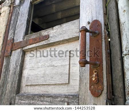 Old wooden door with rusty knob - stock photo