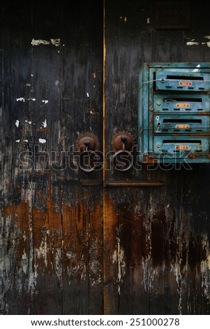 Old Wooden Door with rusty mail boxes on the wall. Background and Texture for text or image. - stock photo