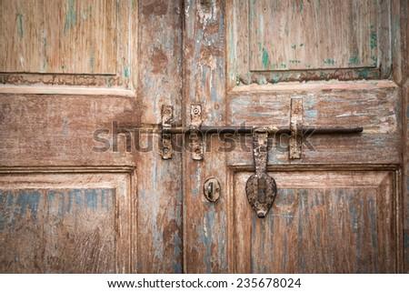 Old wooden door with rusty metal lock and handle - stock photo