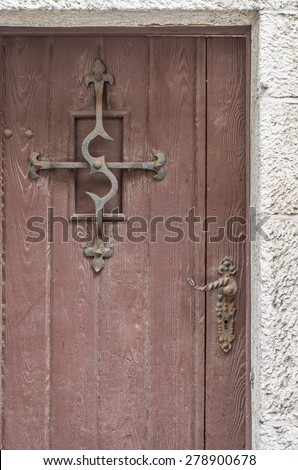 Old wooden door with steel s-shaped grille and portal carved in stone