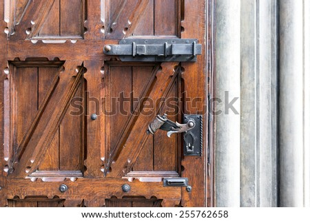 Old wooden door with wrought iron handle in the building of Old Riga - stock photo
