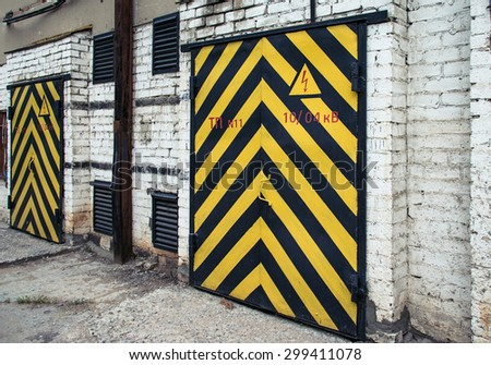 old wooden door with yellow and black stripe - stock photo