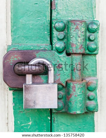 Old wooden doors are locked with a metal padlock. - stock photo