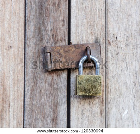 Old wooden doors are locked with a padlock. - stock photo
