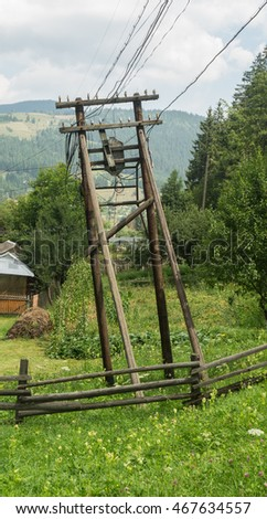 Old wooden electric pole with wires and insulators on the background of mountains