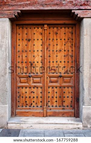 Old wooden entrance door in Alcala de Henares, Madrid - stock photo