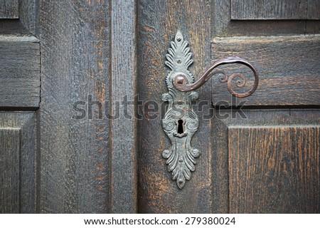 old wooden entrance door with antique door handle - stock photo