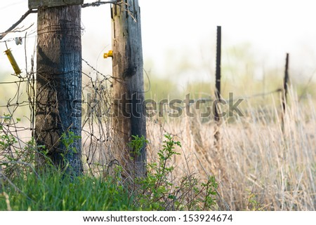Old Wooden Fence Line on a Farm Field in the Morning Light