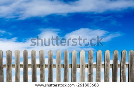 old wooden fence on a blue sky background - stock photo