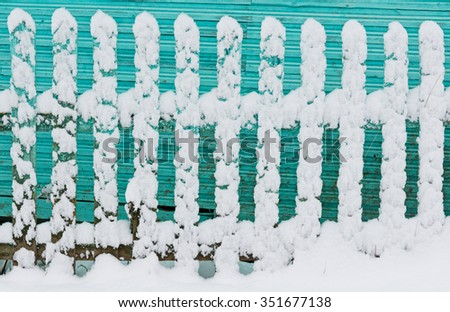 Old wooden fence painted in turquoise color covered with flakes of snow.  - stock photo