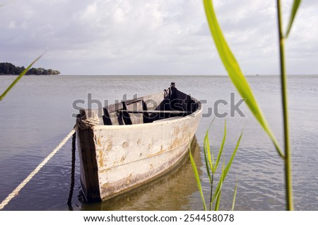 Old wooden fishing boat floating on sea water - stock photo