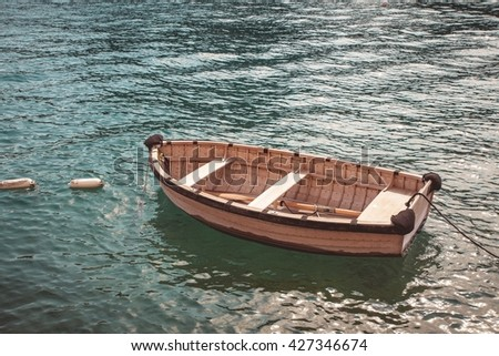 Old wooden fishing boat in turquoise water. Vintage style. - stock photo