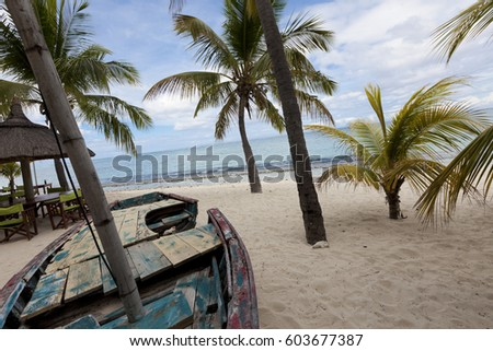 Old wooden fishing boat on a tropical paradise island with ocean and coconut palm trees in the background