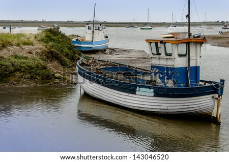 Old wooden fishing boat on mud flats at Brancaster Norfolk England - stock photo