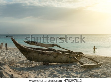 old wooden fishing boat on Zanzibar sandy beach with sunset ocean on the background