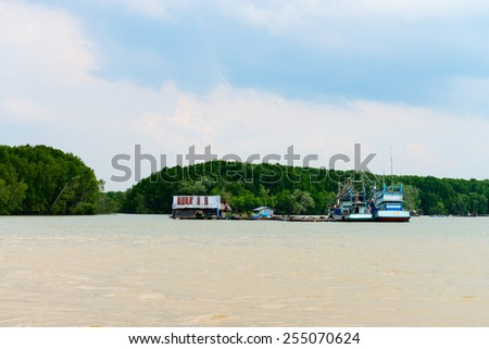 Old wooden fishing village with two ships in wide river water - stock photo