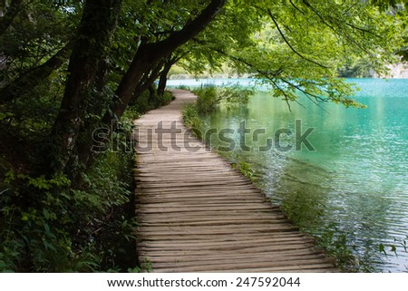 old wooden footpath with blue water grass and trees in National Park Plitvice Lakes in Croatia - stock photo