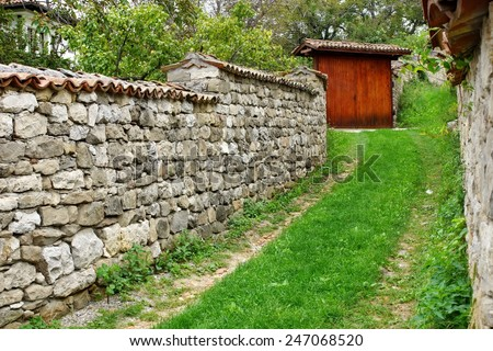 Old Wooden Gate and Stone Fence in Old Town - stock photo