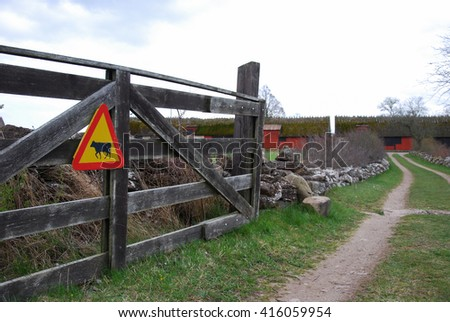 Old wooden gate by a country road with a cattle warning sign