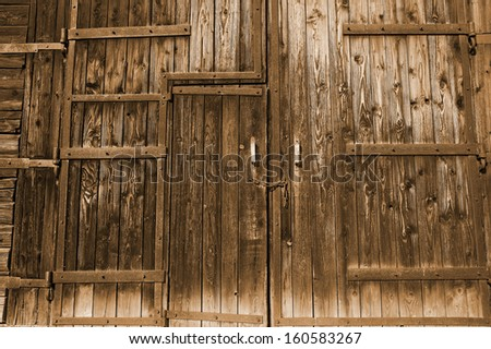 Old wooden gate faded by sun with chain