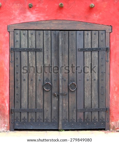 old wooden gate in a red brick wall - stock photo