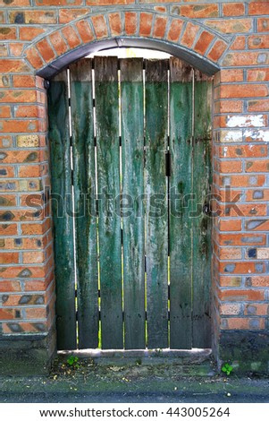 Old wooden gate in an old brick building.