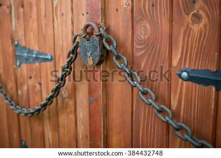 old wooden gate with forged lock and chain - stock photo