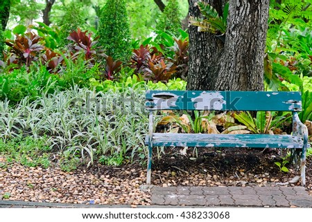 Old wooden green bench in city park - stock photo