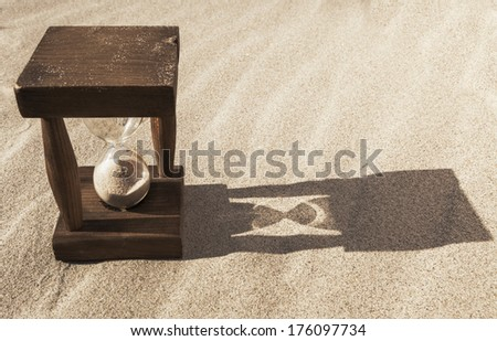 Old wooden hourglass in the sand with morning long shadow - stock photo