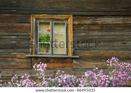 Old wooden house and flowers in window