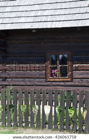 Old wooden house detail with small window and fence