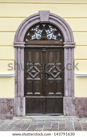 Old wooden house entrance with stone arch. - stock photo