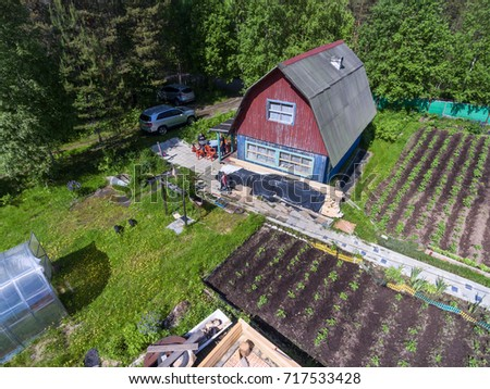 Old wooden house for Russian family with parking lot. Traditional homestead in Russia in forest. Top view