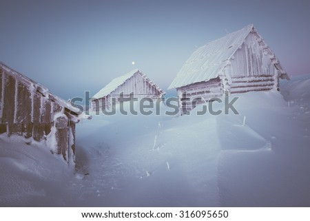 Old wooden house in a mountain village. Morning twilight. Winter landscape with snow drifts. Color toning. Low contrast - stock photo