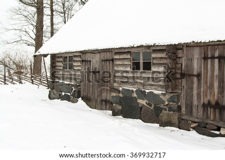 Old wooden house in the snow