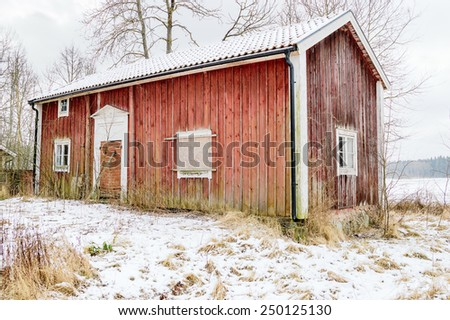 Old, wooden house in winter. The house is abandoned and closed. It has red walls and white corners. Snow on the ground and on roof. - stock photo