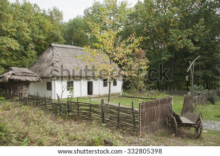 Old wooden house with reed roof in the forest - stock photo