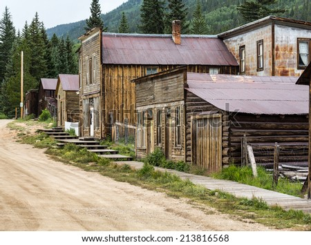 Old wooden houses line the main street of ghost town of St Elmo in Colorado - stock photo