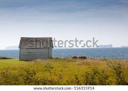 """Old wooden hut near the sea in Gaspesie,Canada. The famous rock """"roche perce"""" in background - stock photo"""