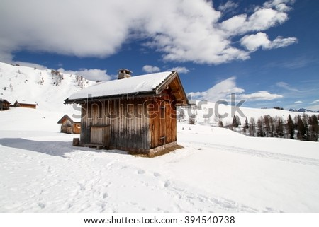 old wooden hut on a winter snowy Dolomites landscape - stock photo
