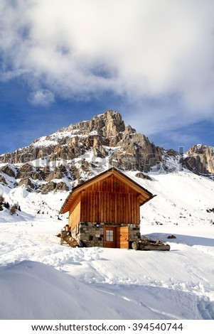 old wooden hut on a winter snowy Dolomites landscape