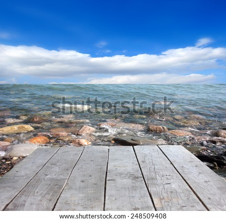 old wooden jetty and rocky shore ocean - stock photo