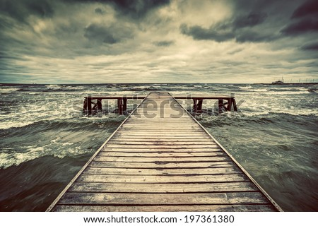Old wooden jetty, pier, during storm on the sea. Dramatic sky with dark, heavy clouds. Vintage - stock photo