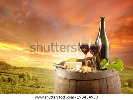 Old wooden keg with bottle and glass of red wine. Rural vineyard on background - stock photo