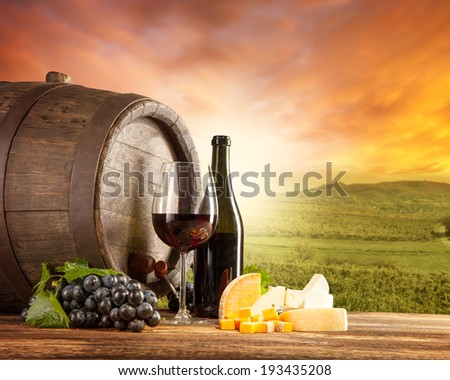 Old wooden keg with bottle and glass of red wine. Rural vineyard on background