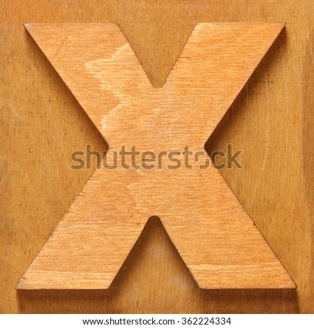 Old wooden letter X on wooden background. One of full alphabet type set