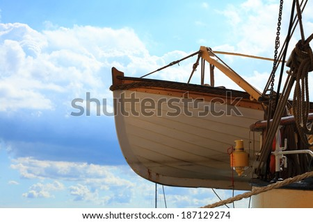 Old wooden lifeboat on a ship blue sky background - stock photo